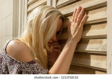 Blonde haired woman leaning on window blinds, sad and depressed