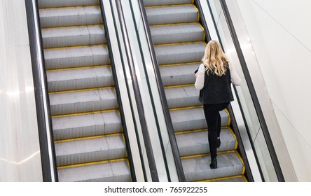 A blonde haired woman, wearing a black vest, riding up an indoor escalator.