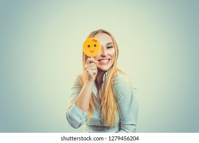 Blonde haired young woman girl playing with yellow emoji candy on a stick standing isolated on light green yellow background playful covering eye, happy smiling, positive human emotion face expression