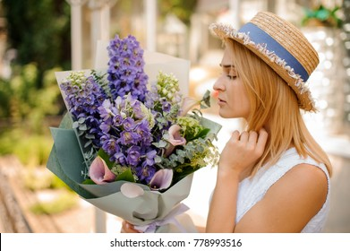 blonde handsome woman in white dress and straw hat holds a bouquet of callas and delphinium packed in grey wrapping-paper