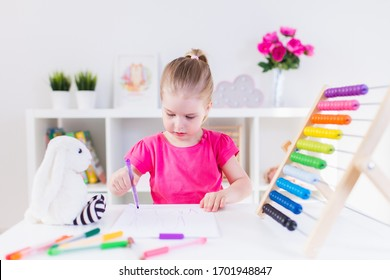 Blonde happy little girl drawing siitting by the white table in light room with wooden colorful abacus. Preschool education, early learning