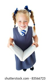 Blonde happy schoolgirl in blue dress and matching tie reads textbook, isolated on white