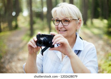 Blonde happy senior woman with photocamera photographing curious stuff in the forest during chill