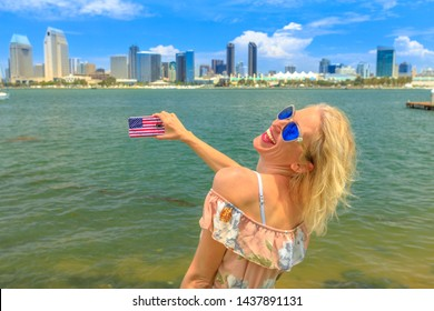 Blonde happy tourist takes photo of San Diego By skyline by mobile phone with American flag cover. Woman lifestyle takes picture in California summer holidays with smartphone from Coronado Island, USA