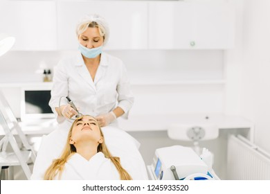 Blonde happy woman receiving ultrasonic facial massage on ultrasound face machine. Female has electric facial lift treatment at luxury spa salon.