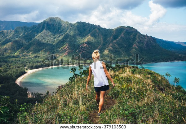 Blonde hiker looks over the ocean on a classic Hawaiian hike.
