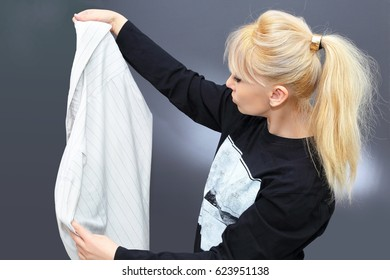 The blonde is holding a man's shirt.The model collects linen for washing. Beauty blonde carefully examines the man's shirt. Girl in a T-shirt on a gray background. Place for text on T-shirt of model.