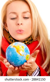 Blonde holds globe in hands and blows on it.