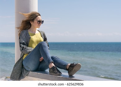 Blonde in jeans and sunglasses sits on a parapet near the sea shore