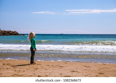 Blonde kid dressed in neoprene looks out to sea from the beach