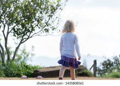 Blonde kid girl standing backwards for play at playground