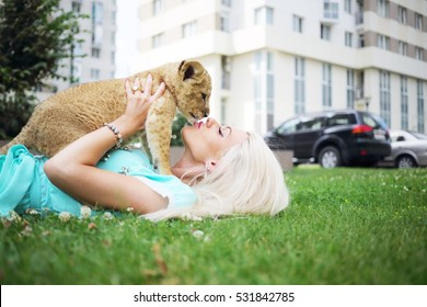Blonde kisses calf of lion and lies on grass near building at summer day