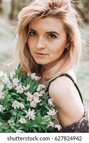 Blonde lady with deep hazel eyes and bouquet in her arms
