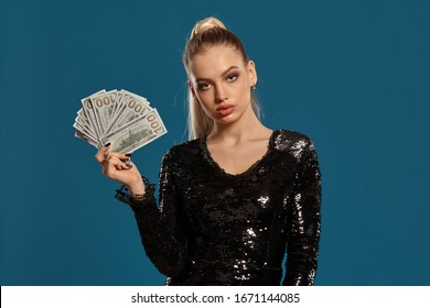 Blonde lady with ponytail, in black sequin dress. Showing fan of hundred dollar bills, posing on blue background. Gambling, poker, casino. Close-up