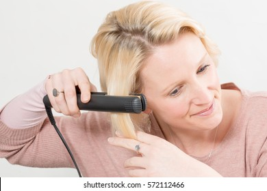 Blonde lady straightening her hair with a hot iron over white background