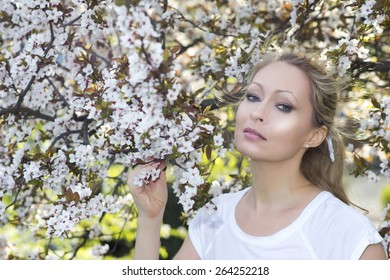 Blonde lady with white blooming tree
