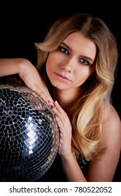The blonde laying in the style of Abba holds a disco ball. The era of disco. Night club, dancing