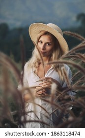 The blonde in a linen dress walks among herbs and wildflowers on a meadow in the mountains. A woman in the Boho style, resting in the countryside, a simple village lifestyle
