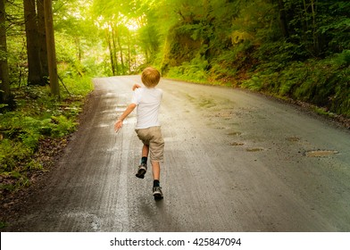 A blonde little boy run on a road in the forest