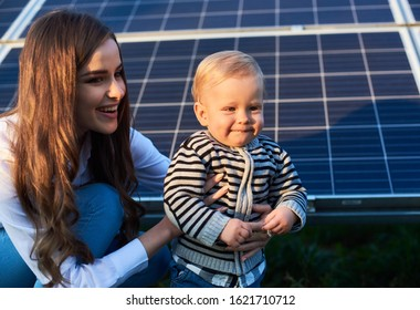 Blonde little child next to her smiling mom looks forward under the sun's rays of the sunset against the background of solar panels. Close up. Young beautiful woman holds a baby