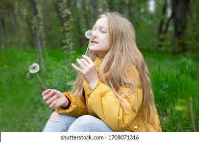 blonde Little girl blowing on dandelions. spring holidays and mood