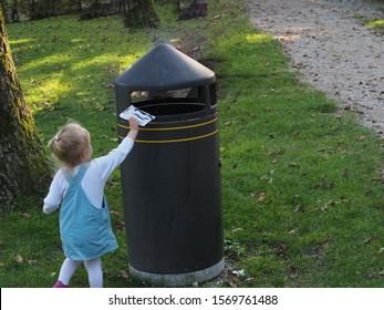 Blonde little girl disposing rubbish into a public litter box