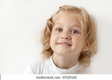 Blonde little girl dressed in white biting her lip on  white background