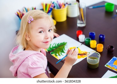 Blonde little girl painting with paintbrush