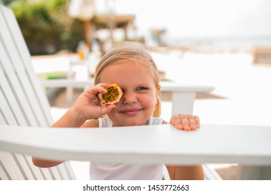 Blonde little girl sitting in chair on beach holding passion fruit in front of her eye with pucker face