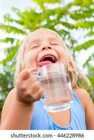 Blonde little girl wearing blue dress holding cup of fresh water with her eyes closed in a summer garden