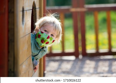 Blonde little toddler child inwearing protective mask, playing on the playground, spring sunny day