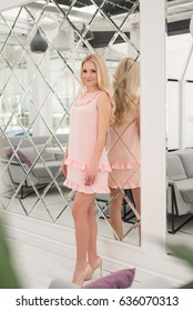 Blonde with long hair in a pink dress in a cafe
