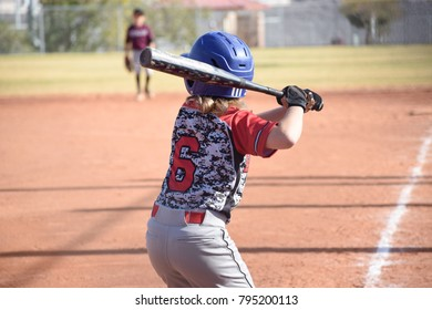 blonde long hair youth baseball player up to bat