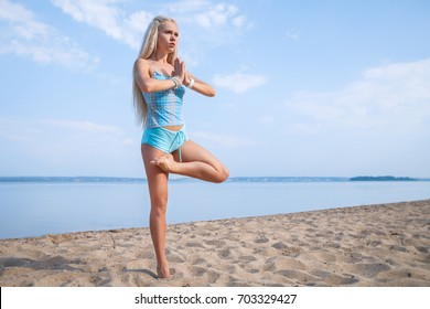 Blonde long haired girl in a blue suit is stretching and doing yoga on a lovely beach in sunlight of the rising sun