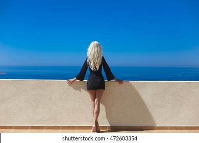 Blonde long healthy wavy hair. Attractive blond back woman standing on balcony looking on blue sky.
