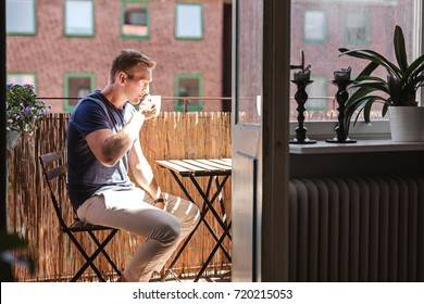 A blonde man enjoying his coffee on a sunny summer morning sitting down outside on his balcony. Photo from inside apartment looking out.