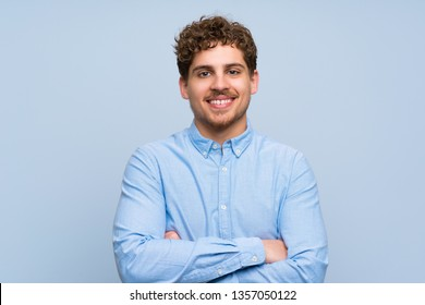Blonde man over blue wall keeping the arms crossed in frontal position