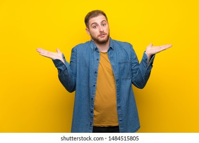 Blonde man over isolated yellow wall making doubts gesture