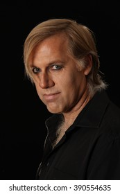 a blonde man with short hair and a long fringe wearing a black shirt and artistic make-up to create a younger contoured look with shadows