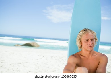 Blonde man sitting on the beach with his surfboard while looking towards the side