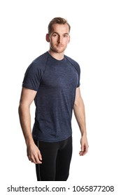 Blonde man wearing workout clothing standing against a white background staring at camera.