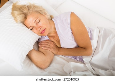 Blonde mature female sleeping on white pillow in bed at home