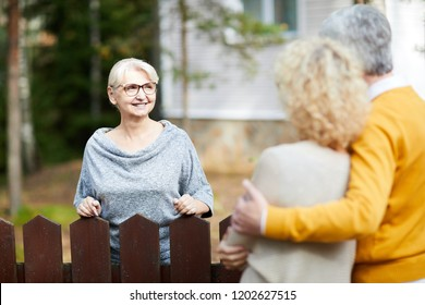 Blonde mature woman in eyeglasses and grey pullover looking at her neighbours during talk through fence