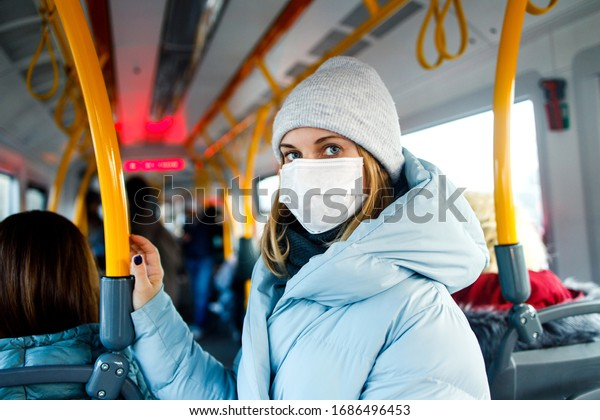 Blonde in medical mask standing in bus lounge next to yellow handrails in afternoon.