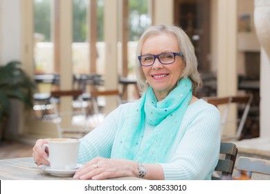 Blonde middle aged woman sitting at cafe with drink