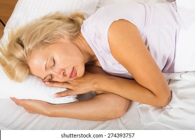 Blonde middle-aged woman sleeping in bed at home