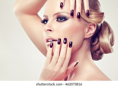 Blonde model  girl  with burgundy manicure  nails . Hairstyle