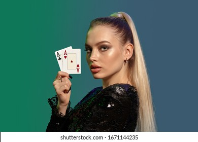 Blonde model with ponytail, in black sequin dress. Showing two aces, posing sideways on colorful background. Gambling, poker, casino. Close-up