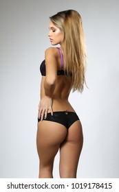 blonde model posing in black, purple lingerie