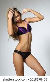 blonde model posing in purple lingerie